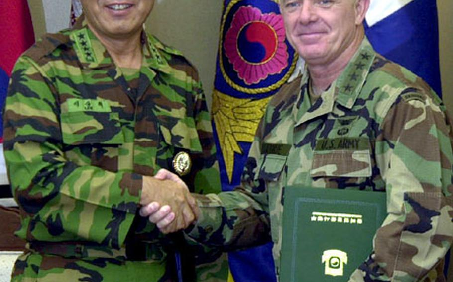 Gen. Lee Sang-hee, chairman of the Republic of Korea Joint Chiefs of Staff, and U.S. Forces Korea commander Gen. Leon J. LaPorte shake hands Wednesday at the Ministry of National Defense after signing letters certifying the transfer of six military missions to the South Korean military.