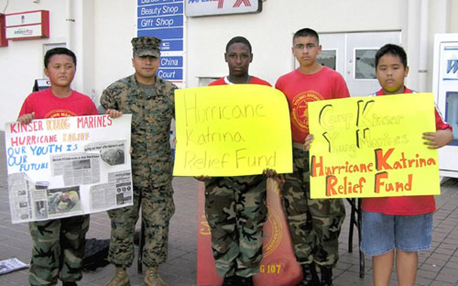 Gunnery Sgt. Guadalupe Perez Jr. and members of the Camp Kinser Young Marines, from left, Richard Deleon, Lee Taylor, Adrian Adame and Kevin Schmidt pose outside the Camp Kinser Exchange with signs they used to raise funds for Hurricane Katrina victims.