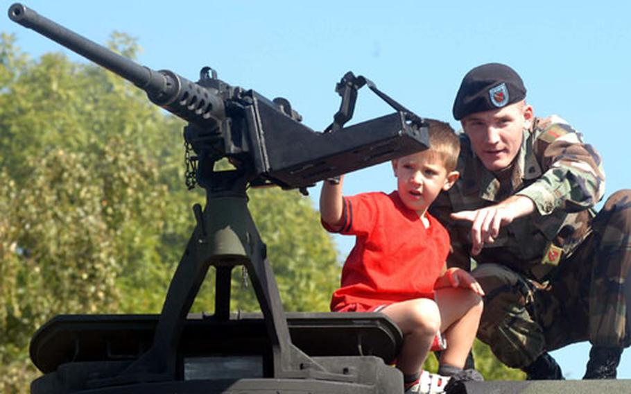 Spc. Jeremy Ende of 1st Battalion 7th Field Artillery out of Schweinfurt, Germany, shows Will Pyle, 4, around an M109A6 Paladin on Thursday at the Land Combat Expo.