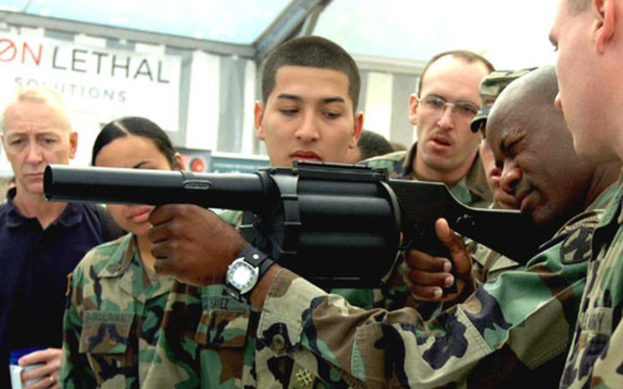 Sgt. 1st Class Malcolm Peeples, second from right, checks out a Multilauncher, a six-shot, spring-loaded, semiautomatic 40mm grenade launcher at the Land Combat Expo 2005 in Heidelberg, Germany, on Thursday. Peeples is with the 529th Military Police Company in Heidelberg.