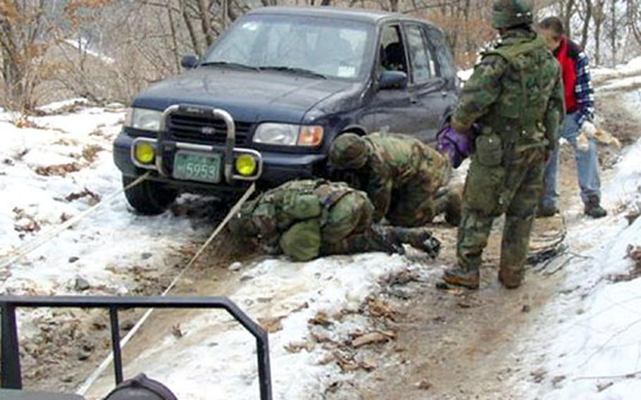 Soldiers from the 2nd Infantry Division attach a line to Kim Soung-ho's vehicle to pull it from a snow bank on Mount Bojang in March.