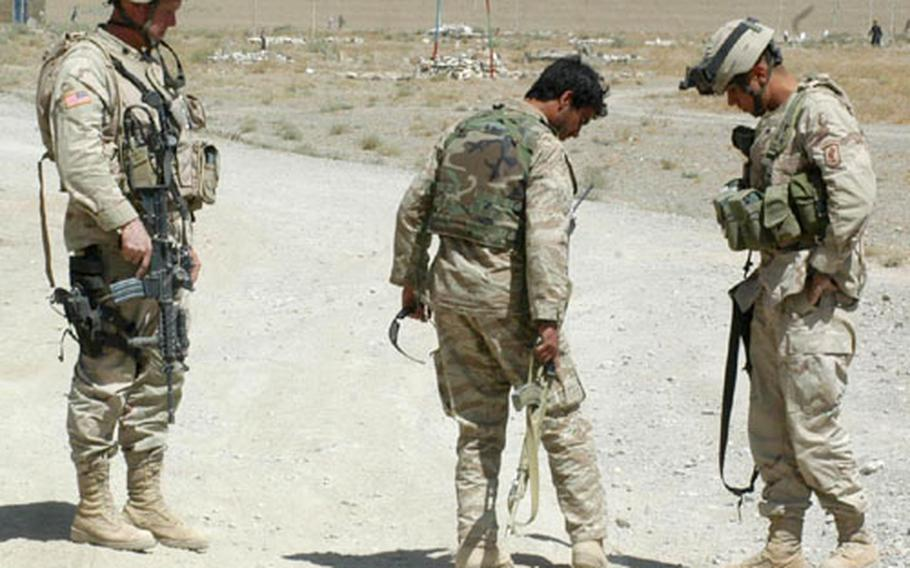 Sgt. Kyle Seitz and translator Noor Ullah examine a patch of road that two locals suspected might contain an improvised explosive device, while Lt. Col. Tim McGuire observes during an election-day patrol.