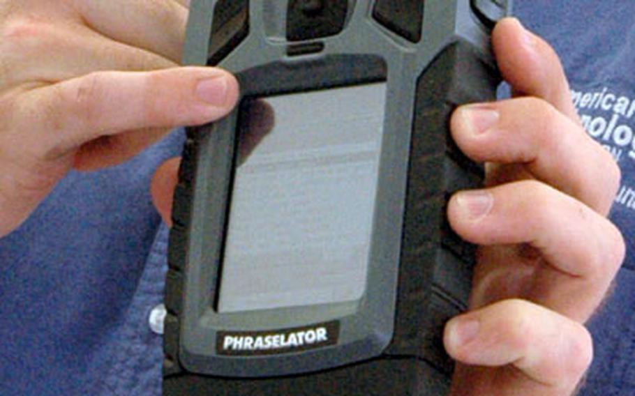 """Ryk Williams of American Technology Corporation shows off the Phraselator, a device that can translate and broadcast commands and questions, like """"do you have a weapon?"""" in up to 50 languages."""