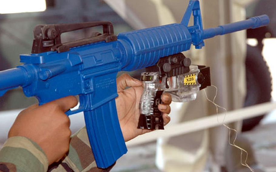 A Taser X26 non-lethal weapon, attached to a mock-up of an M-4 rifle. The Taser immobilizes the target through electric shocks.