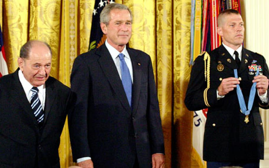 Tibor Rubin, President Bush and a military attache listen to the reading of Rubin's Medal of Honor citation.