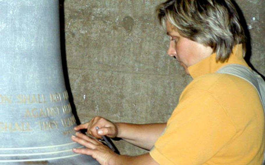 """A German craftswoman epoxies the inscription on the English-language bell. The larger of the two bells has the crest of the 222nd Base Support Battalion, the chaplains' regimental crest and a quote from the Book of Isaiah — """"Nation shall not lift up sword against nation, neither shall they learn war any more."""""""