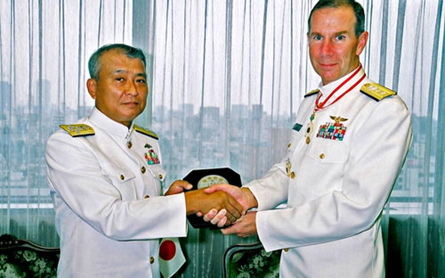 Rear Adm. Frederic R. Ruehe, commander of Naval Forces Japan, right, receives the Order of the Rising Sun, Gold and Silver Star from Japan Maritime Self Defense Force chief of staff Adm. Takashi Saito on Tuesday, on behalf of the Emperor.