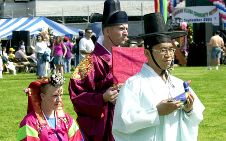 Maj. Stacie Hatten and her husband Glen participate in the re-creation of a traditional Korean wedding during the Hannam Village Community Festival on Saturday.