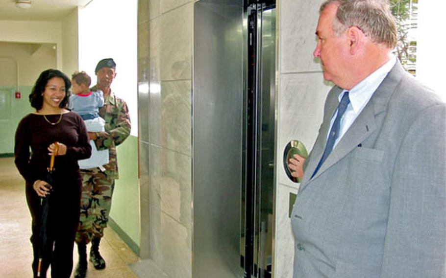 Area IV housing chief Charles Youngblood, right, holds a newly installed elevator to allow residents to take the first ride on Friday at Camp George in Daegu, South Korea. Boarding the elevator are fourth-floor residents Anastasia Brown and her husband, Chief Warrant Officer Cameron Brown, who holds their seven-month-old son Christian.