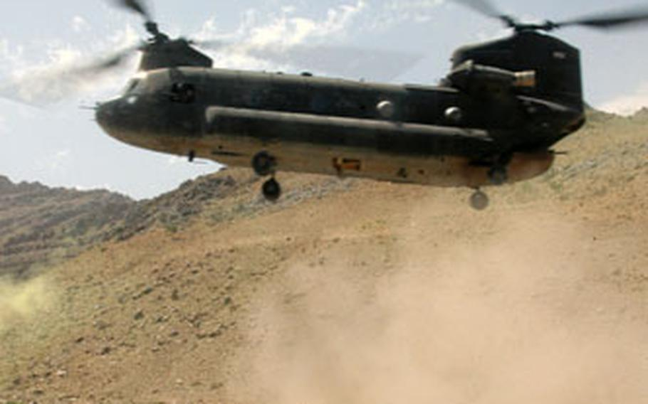 Soldiers from Company C, 2nd Battalion (Airborne), 503rd Infantry Regiment, turn and kneel away from a CH-47 Chinook helicopter as it comes in for a landing in a riverbed northwest of Qalat, Afghanistan, in July. A similar Chinook helicopter crashed southwest of Deh Chopan on Sunday, killing all five crewmembers.