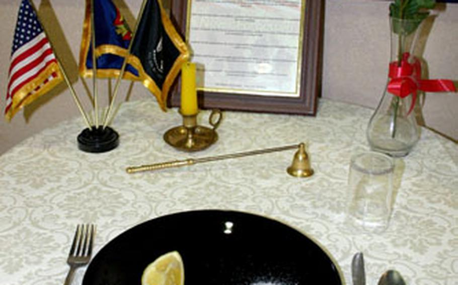 A missing man table is always present in a corner of the galley at the Capodichino Naval Support Activity Naples, Italy. Each item holds symbolic meaning, such as the slice of lemon on a plate signifying the bitter fate of those captured and missing.