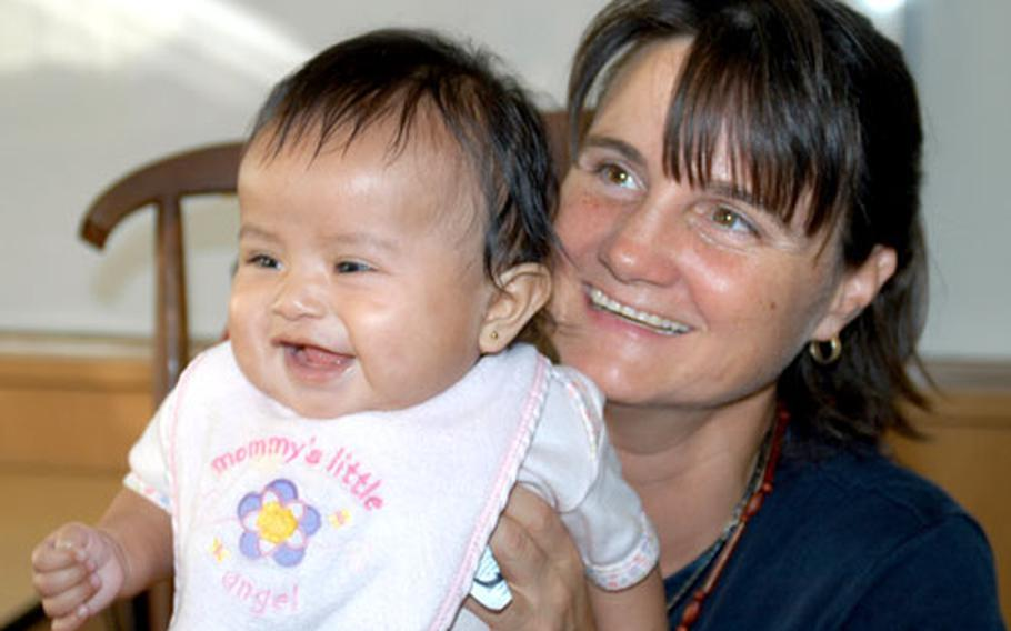 Sollars Elementary School teacher Tracy Rice holds her 4-month-old daughter, Cathy, whom she adopted this summer from the Macushi Amerindian tribe in Guyana, South America. The adoption will be finalized in November.