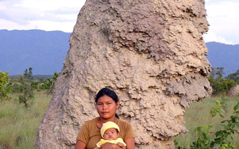 Cathy Rice's biological mother, Seleen Mario, holds Cathy in July in front of a giant termite mound near their tribe's home in Moco Moco Village.