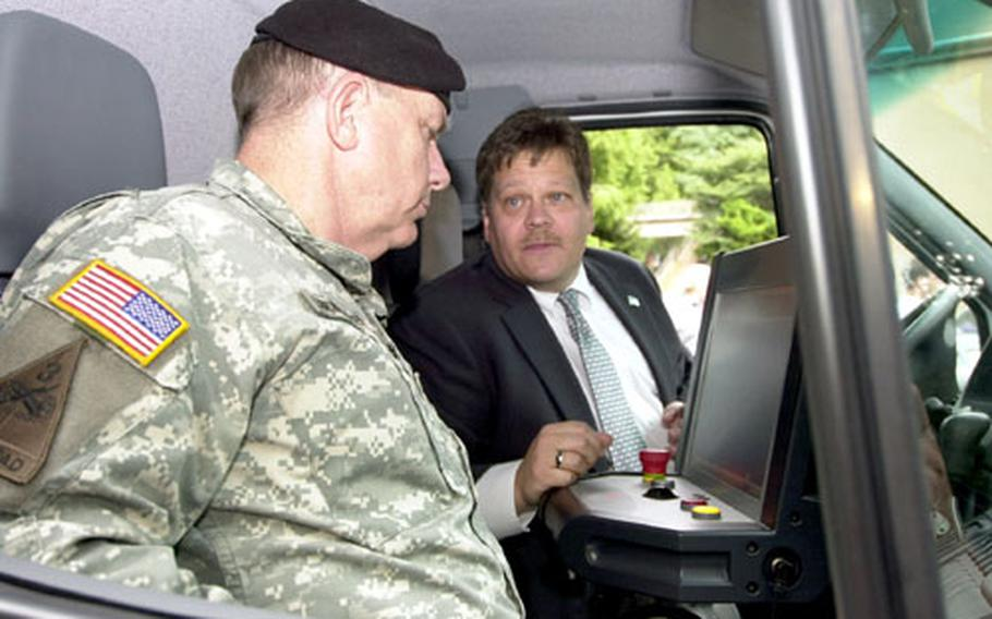 Robert Britton, a technical training specialist with American Science and Engineering, Inc., explains how the Z Backscatter Van works to Brig. Gen. Harvey T. Landwermeyer, commander of Korea Region Office, Installation Management Office, during a demonstration Friday. Area II purchased one of the vans to bolster force protection.