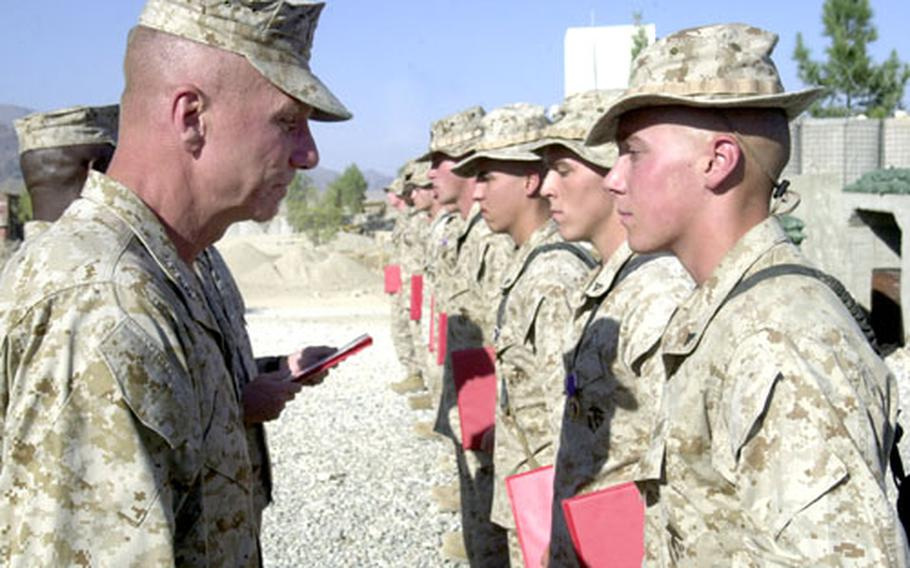 Marine Corps Commandant Gen. Michael W. Hagee, left, prepares to give a combat meritorious promotion to Joseph P. Thomas, right, to the rank of corporal. Thomas also received a Purple Heart. Pictured down the line from Thomas are eight fellow Marines from Company F, 2nd Battalion, 3rd Marine Regiment, 3rd Marine Division, who received Purple Hearts on Monday at Forward Operating Base Mehtar Lam in Afghanistan.