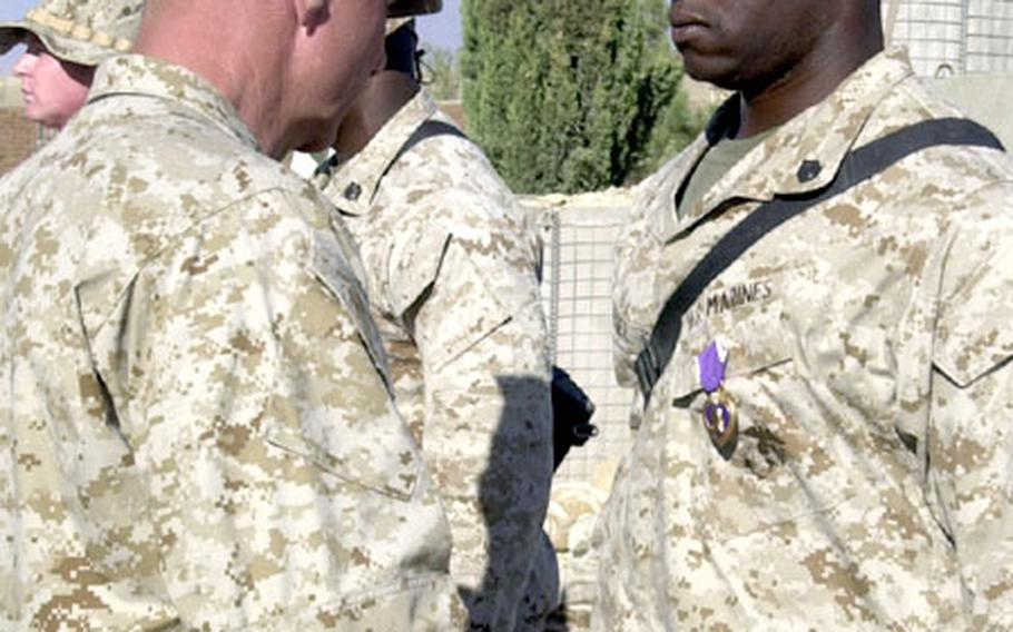 U.S. Marine Corps Staff Sgt. Kevin B. Walker, right, prepares to shake hands with Marine Corps Commandant Gen. Michael W. Hagee shortly after Walker received a Purple Heart.