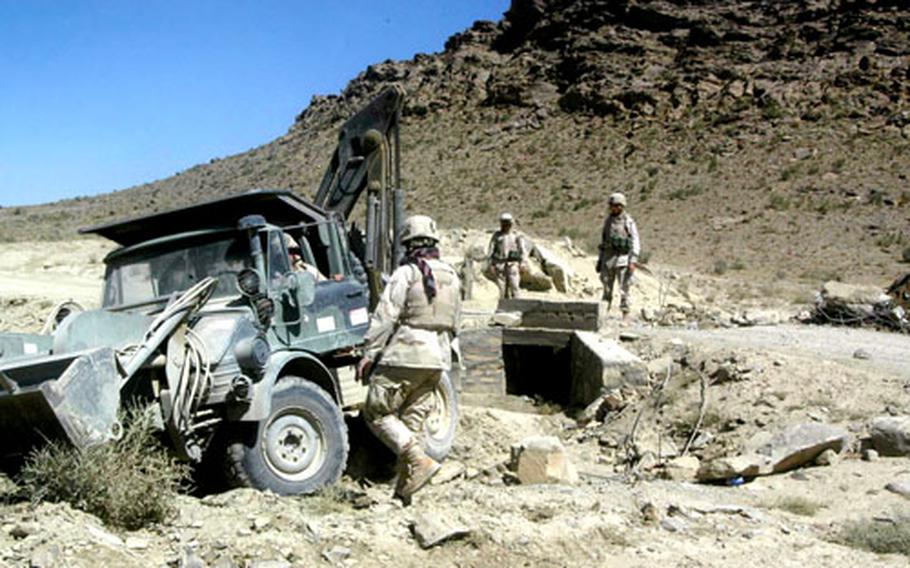 Soldiers from Company B, 864th Engineer Battalion from Fort Lewis, Wash., get ready to demolish part of a bridge spanning a section of the road to be replaced in Paktika province.