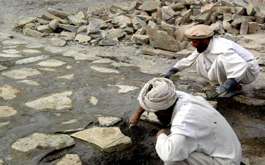 Afghan workers mix stones and concrete to build a cobblestone road in Orgun — the first such road in Paktika province. An Afghan contractor is doing the work thanks to money from the U.S. Army.