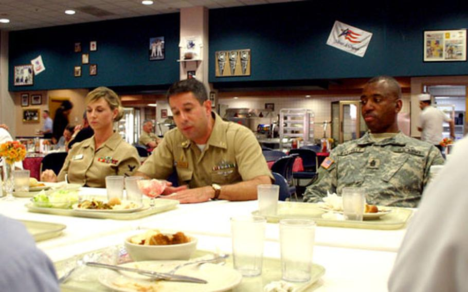 Sgt. Maj. Michael Bartelle, right, and Master Chief Anthony Evangelista, center, talk with sailors Wednesday during a luncheon at the Capodichino Naval Support Activity Naples, Italy.