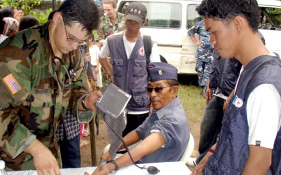 A U.S. medic from the Joint Special Operations Task Force in Zamboanga takes the blood pressure of a Philippine police officer Monday during the Medical Civic Action Program conducted by Philippine and U.S. military personnel in Jolo.
