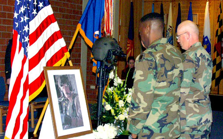 Two soldiers from Giebelstadt, Germany, pay their respects to Sgt. Kenneth Ross of the 12th Aviation Brigade's 7th Battalion, 159th Aviation Regiment, Thursday in Giebelstadt.