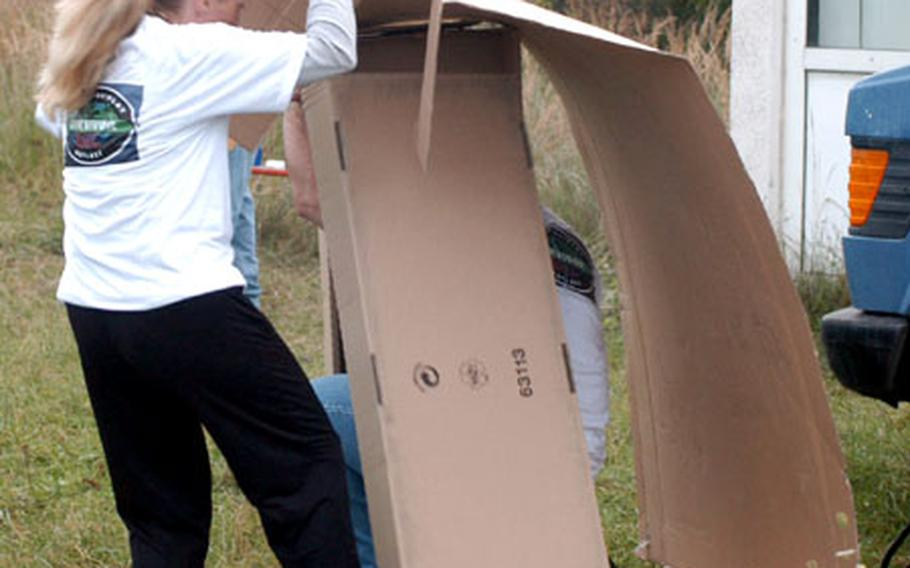 """Heather Leeds and Maj. David Knellinger construct a shelter out of cardboard Wednesday in Bamberg during a """"Survivor""""-style competition judged by three former contestants of the reality TV show."""