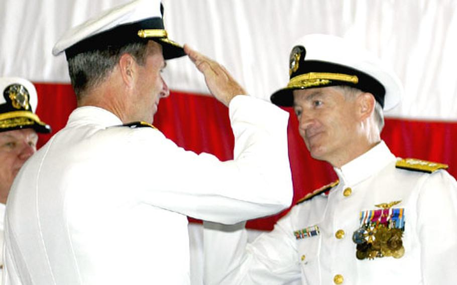 Rear Adm. Frederic R. Ruehe exchanges salutes with Rear Adm. James D. Kelly, who relieved him as commander, U.S. Naval Forces Japan, during a change-of-command ceremony aboard USS Kitty Hawk at Yokosuka, Japan, on Thursday.