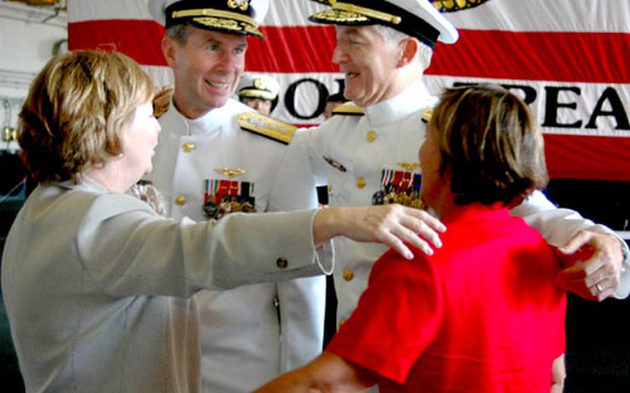 Rear Adm. James D. Kelly, right, and Rear Adm. Frederic R. Ruehe embrace their wives during a reception following their change of command held in the hangar bay of USS Kitty Hawk.