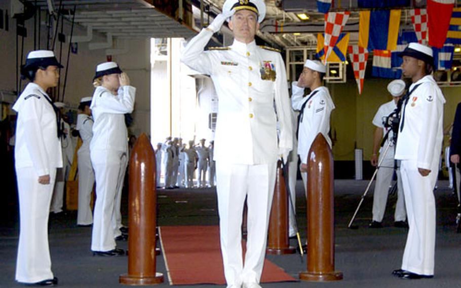 Rear Adm. James D. Kelly pauses after being piped aboard the USS Kitty Hawk for his change-of-command ceremony.