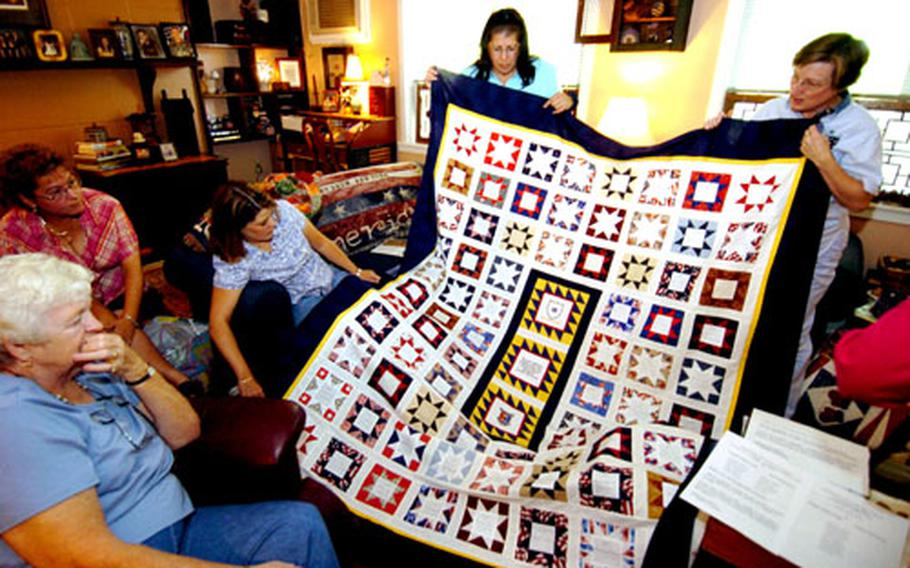Members of the Yongsan Quilters Guild hold up the finished front of a quilt made in memory of the soldiers from the 2nd Brigade Combat Team who died in Iraq.