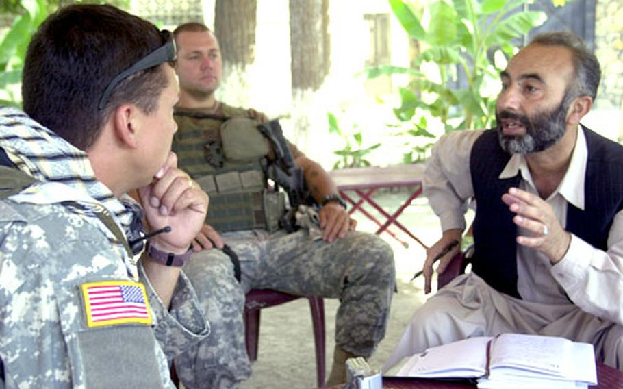 Staff Sgt. Robert Dasher of the U.S. Army Reserves, left, talks with Noories Wodolluh, Laghman province's director of public health, at a recent meeting. Wodolluh was asking that a 200-bed hospital be built near Mehtar Lam, the Laghman province capital. Dasher, who is attached to the Mehtar Lam provincial reconstruction team, told Wodolluh to submit a plan for the project.