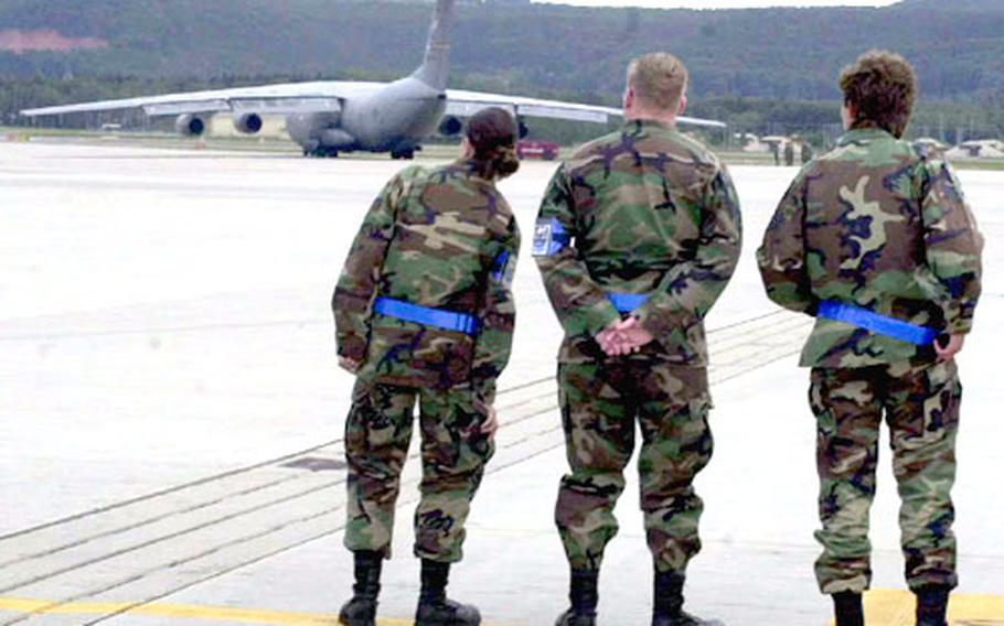 Airmen watch a C-141 Starlifter taxi before take off at Ramstein Air Base, Germany, on Friday.