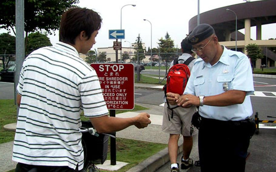 A Japanese civilian guard checks an identification card Friday at Fussa Gate, the main entrance of Yokota Air Base, Japan. Officials from the 374th Security Forces Squadron say Japanese Master Labor Contract employees are the best option for guard duty at Yokota.