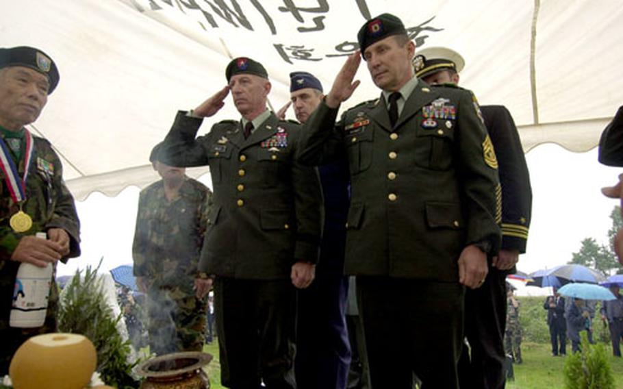 Brig. Gen. Richard W. Mills, who leads Special Operations Command Korea, and Command Sgt. Maj. Sean Rooney salute a memorial to the fallen members of Tiger Brigade.