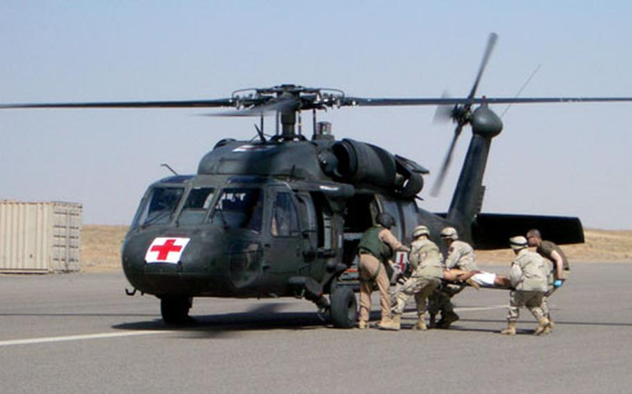 Medics and soldiers from the 1st Battalion, 7th Field Artillery Regiment and the 1st Battalion, 33rd Field Artillery Regiment load a patient onto the airstrip at Forward Operating Base Summerall near Bayji, Iraq, after a car bomb at the base's front gate June 1, 2004. Medics in these units currently are not eligible for the Combat Medical Badge.
