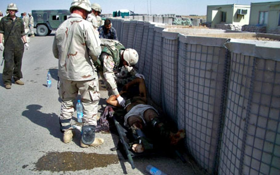 Medics from the 1st Battalion, 7th Field Artillery Regiment treat dozens of wounded Iraqis outside Forward Operating Base Summerall near Bayji, Iraq, June 1, 2004.