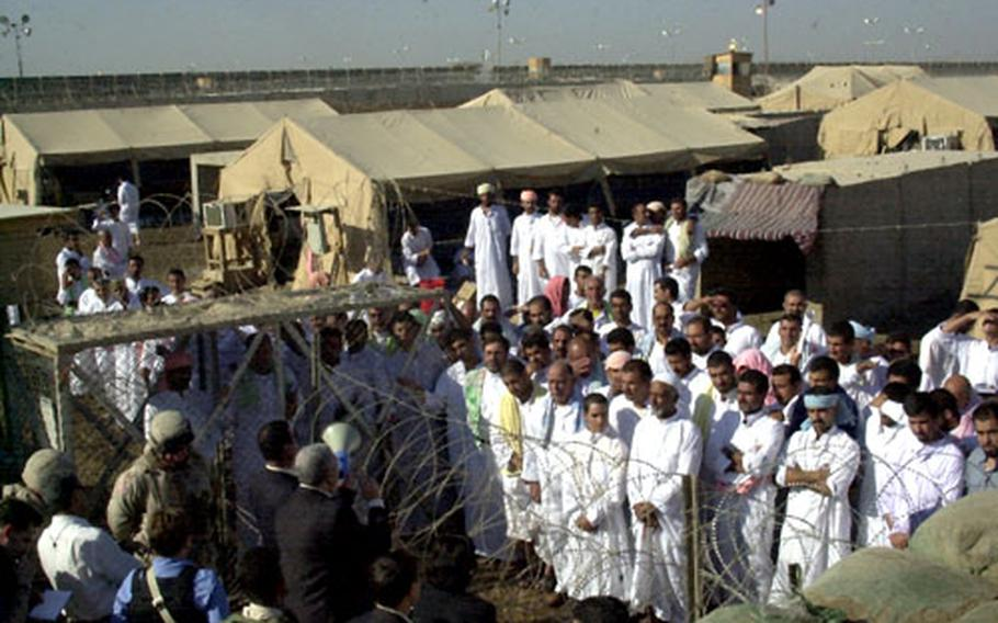 Prisoners listen to Iraqi government officials before their release from Abu Ghraib prison on Saturday.