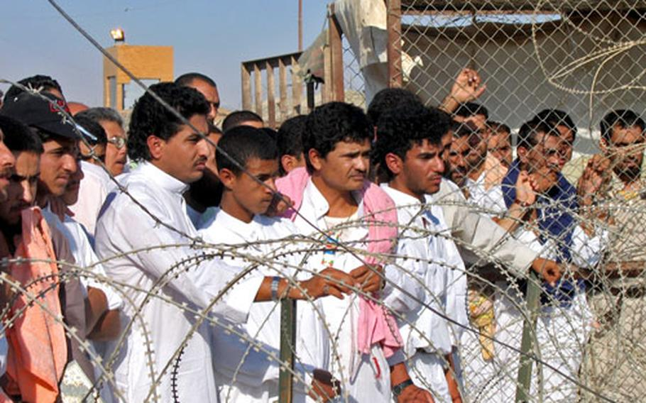 Prisoners wait to be released from Abu Ghraib prison on Saturday.