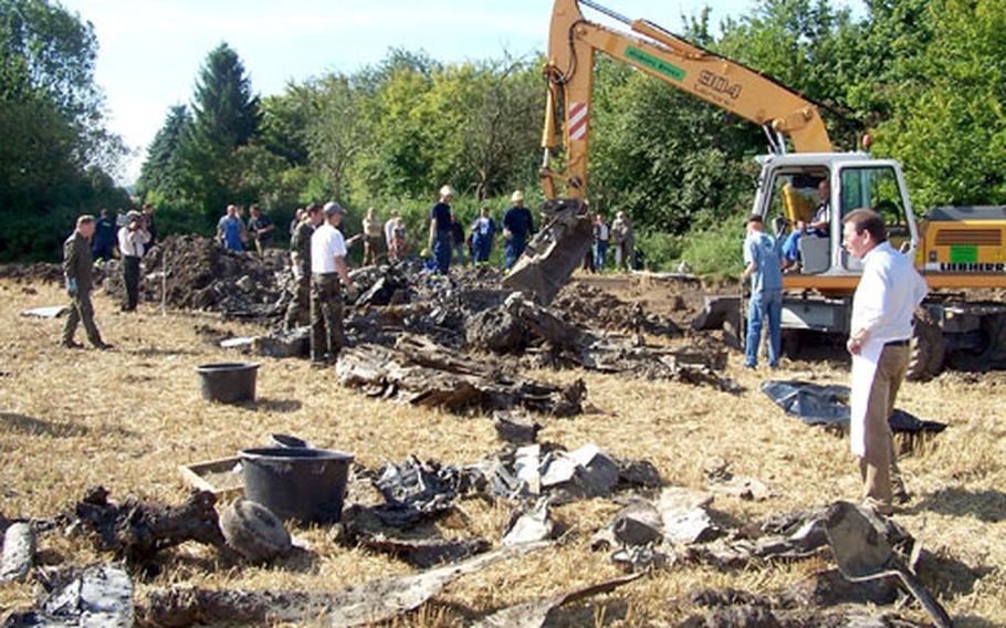Members of Danny Keay's World War II aircraft recovery team work on a site containing the remains of a P-47 Thunderbolt and its pilot near Dortmund, Germany, this summer.