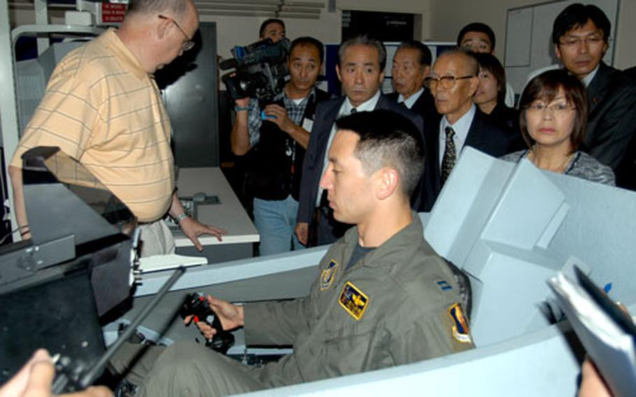 Capt. Kevin Jones, a pilot with the 35th Fighter Wing at Misawa Air Base, Japan, demonstrates a flying procedure in an F-16 simulator for Japanese government and city officials Thursday.