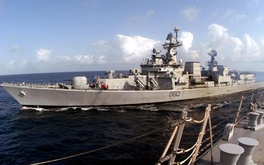 """The Indian destroyer Mysore """"leapfrogs"""" the guided missile destroyer USS Chafee during a training exercise off the coast of India. The Chafee, part of the Nimitz Strike Group, is participating in Malabar 2005."""