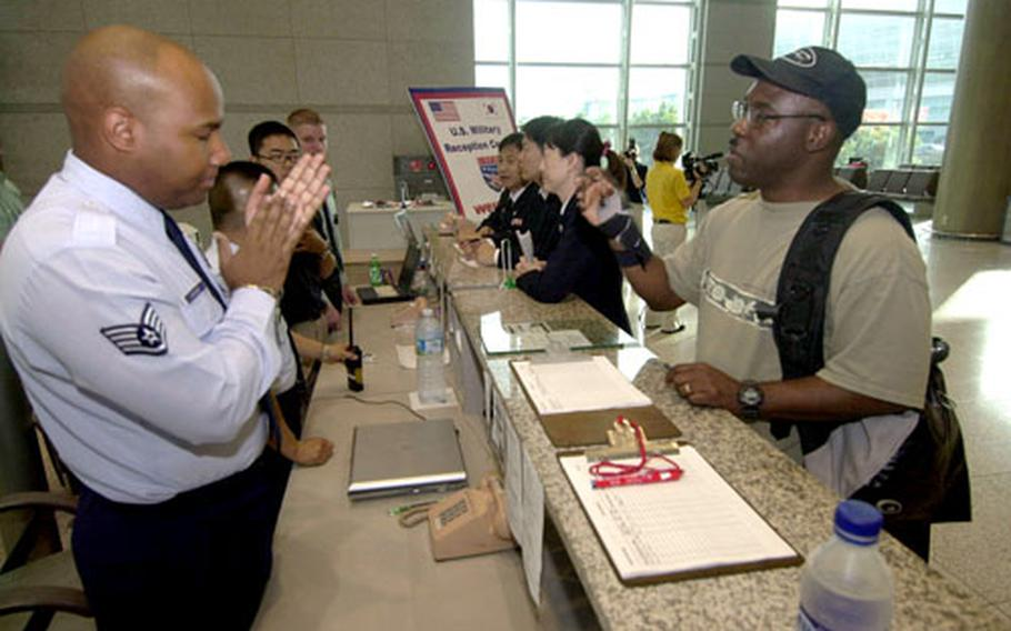 Air Force Staff Sgt. Hugh Archer, left, fields questions Saturday at the reception desk at Incheon International Airport, South Korea.