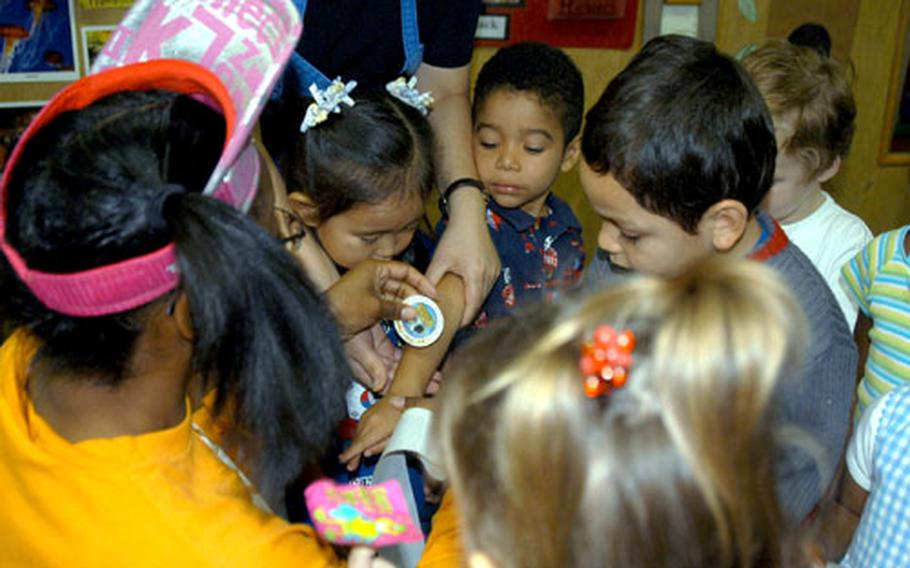 Children clamor to get a sticker from Penelope.