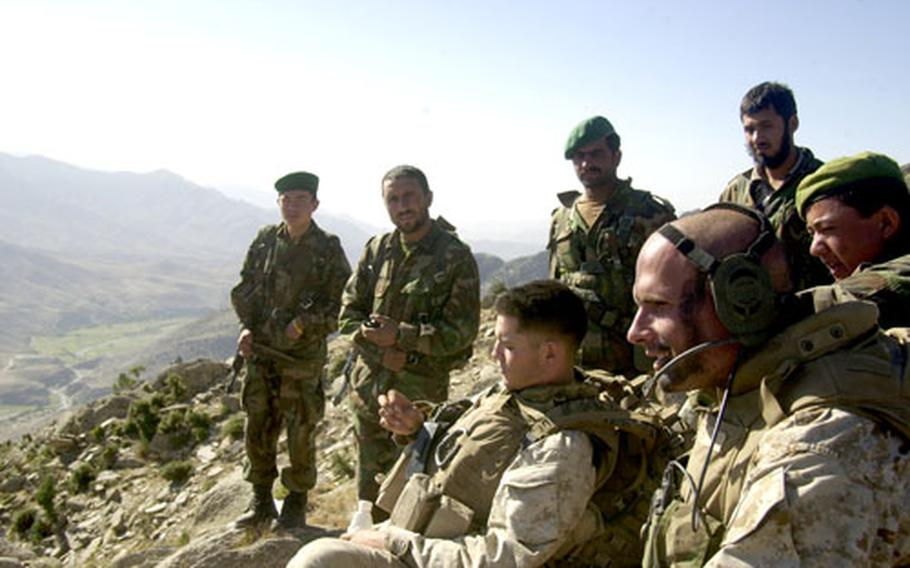 1st Lt. Ryan Cohen, right, weapons light platoon commander of Company F, sits atop the 6,300-foot peak Friday. Members of the Afghan National Army are in the background.