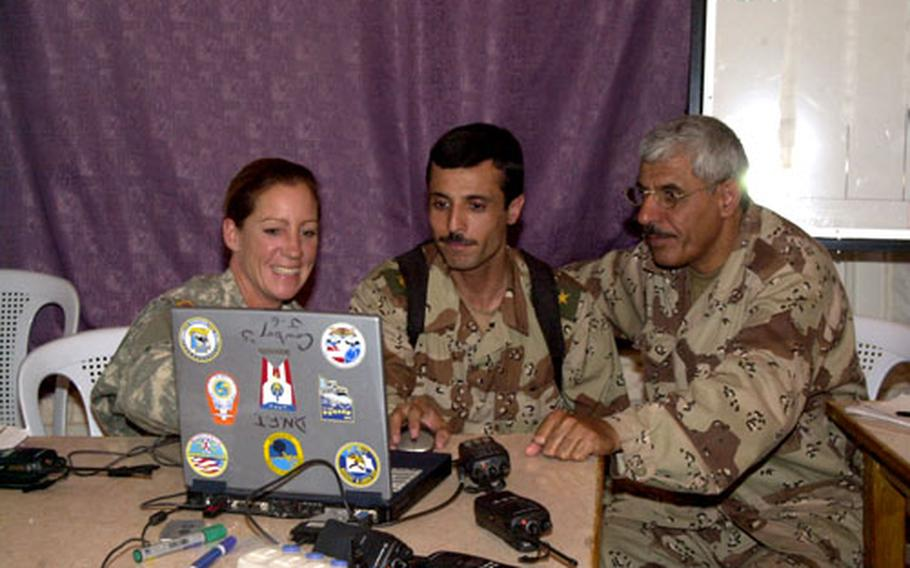 Sgt. 1st Class Janet Baldridge, left, teaches Iraqi soldiers about new communications software at the Iraqi army's 4th Division compound, formerly known as Forward Operating Base Dagger, in Tikrit, Iraq.