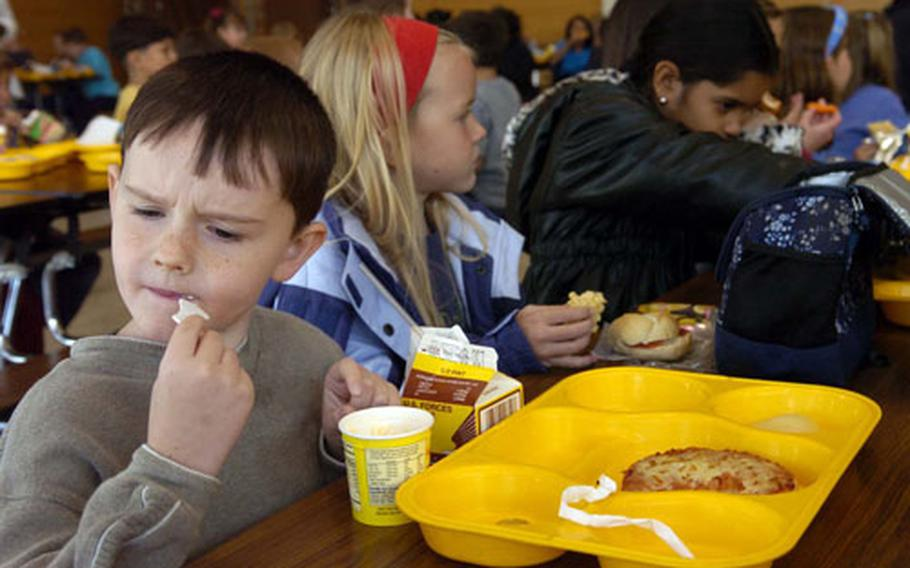 Children enjoy their lunch Friday at Darmstadt Elementary School in Germany. Under new guidelines released by the U.S. Department of Agriculture, more families, though not necessarily these students, may be eligible for the Free and Reduced Lunch program.