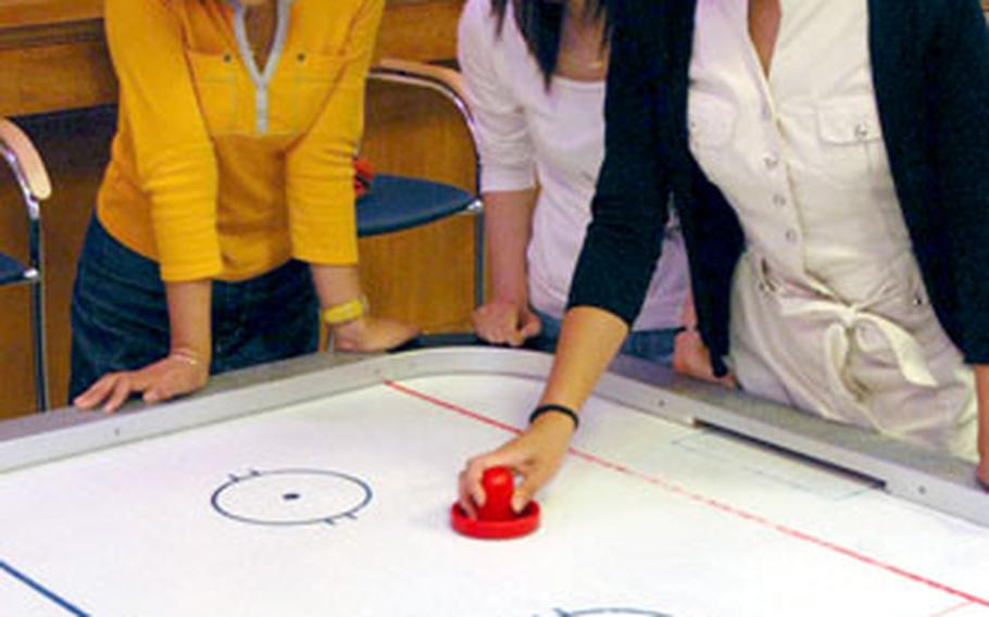 Students from Keimyung University, South Korea, try their hand at air hockey during a visit to the Community Activity Center on Camp Walker last month. About 30 students from the university visited the Area IV Support Activity in Daegu and were given a tour of the installation.