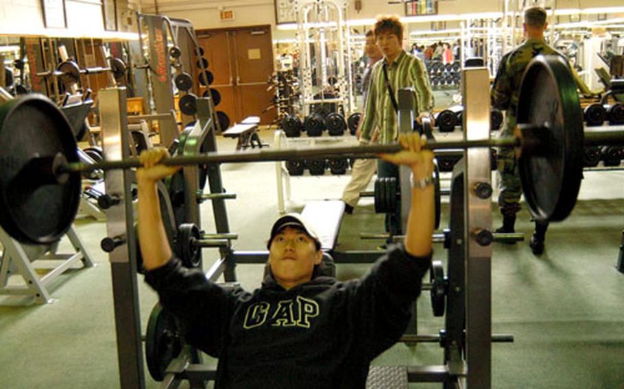 A student from Keimyung University tries out the free weights in Camp Walker's Kelly Fitness Center.