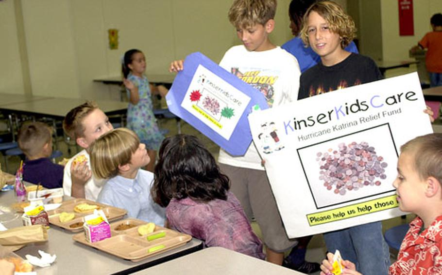 Sixth-grader Roy Beecher, right, and fifth-grader Matt Vohr carry signs asking for hurricane relief donations in Kinser Elementary School's cafeteria Friday at Camp Kinser, Okinawa. Students at the school have collected more than $1,200 for the relief fund.