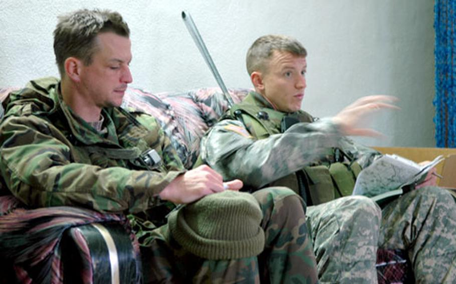 """Capt. Chris Kuzio, right, and his translator talk business with """"Iraqi officials"""" during a training exercise last week at Hohenfels, Germany."""